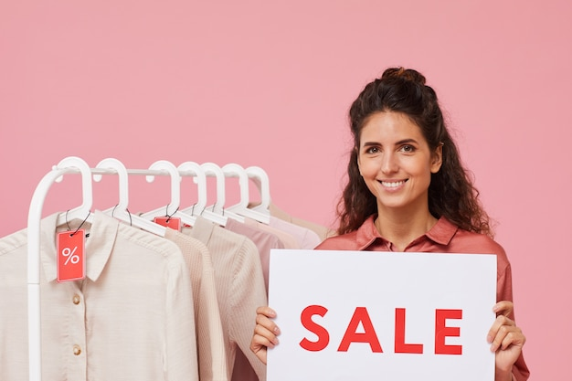 Portrait of young woman with curly hair holding sign with sale and smiling at camera she selling clothes