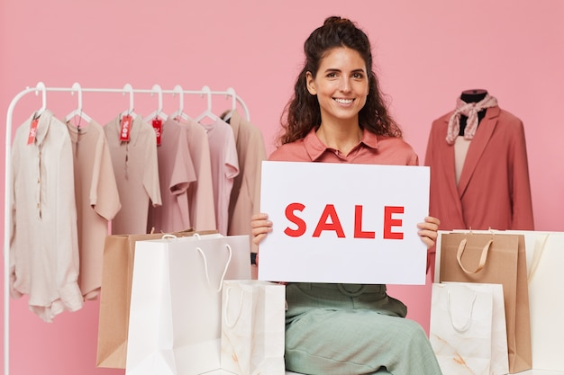 Portrait of young woman with curly hair smiling and holding sale placard while standing in the shop
