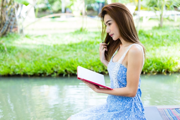 Portrait young woman with diary in park
