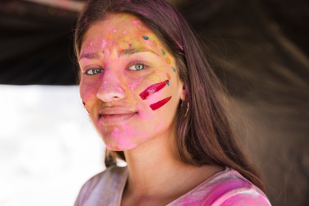 Portrait of a young woman with face painted with holi color