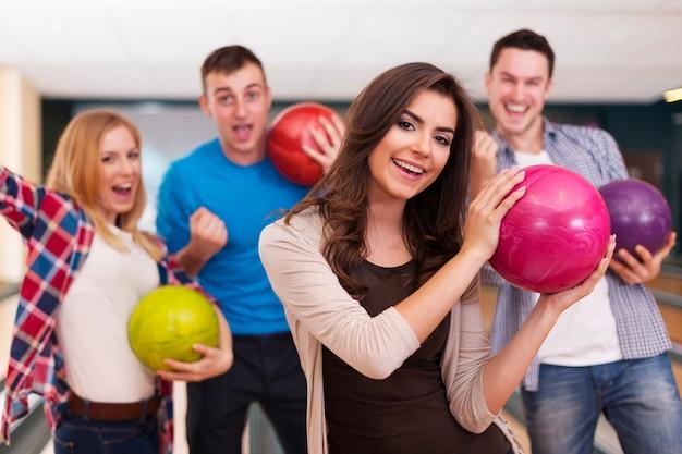 Ritratto di giovane donna con gli amici al bowling