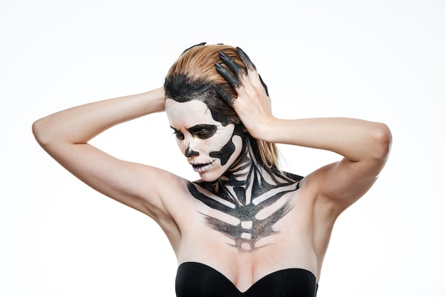 Portrait of young woman with frightening halloween makeup posing over white background