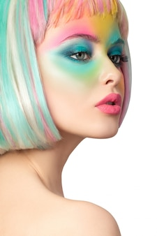 Portrait of young woman with funny rainbow coloured make-up
