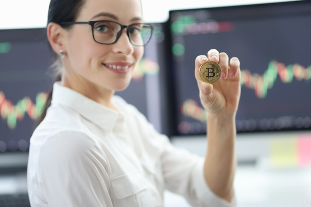Portrait of young woman with glasses holding bitcoin against background of financial indicators