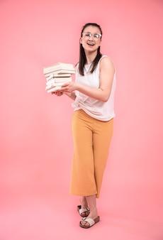 Ritratto di una giovane donna con gli occhiali su uno sfondo rosa a figura intera. concetto di educazione e hobby.