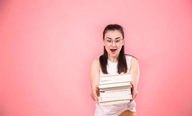 Ritratto di una giovane donna con gli occhiali su uno sfondo rosa con libri nelle sue mani.