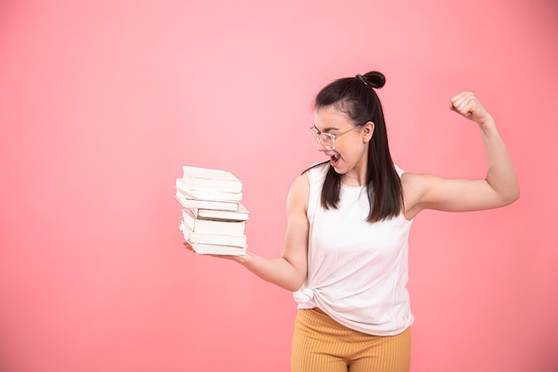 Portrait of a young woman with glasses on pink with books in her hands