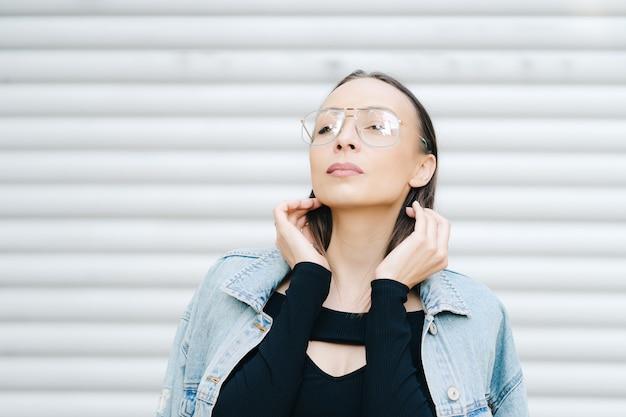 眼鏡をかけた肖像画の若い女性。デニムジャケットを着た長い黒髪のかわいいスタイルの女性。