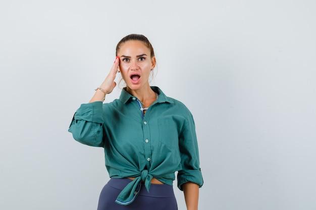 Ritratto di giovane donna con la mano sul lato del viso in camicia verde e guardando la vista frontale scioccata