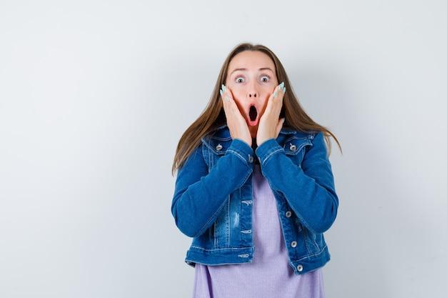 Ritratto di giovane donna con le mani sulle guance in maglietta, giacca e vista frontale scioccata