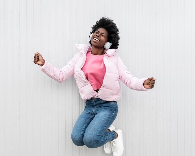Портрет молодой женщины с прыжками в наушниках