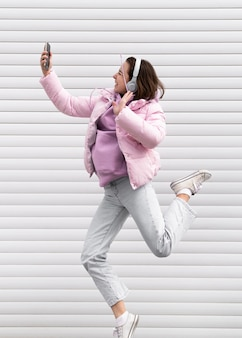 Portrait young woman with headphones jumping