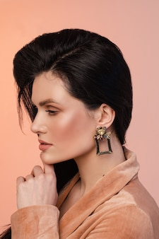Portrait of young woman with healthy skin and black square earrings isolated on pink wall