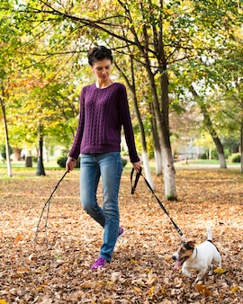 Portrait of young woman with her dog in the park