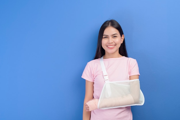 A portrait of young woman with an injured arm in a sling over blue wall