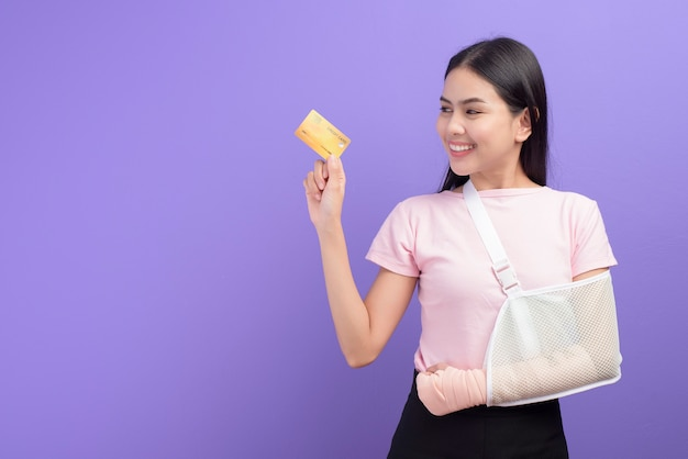 Portrait of young woman with an injured arm in a sling holding a credit card over purple wall
