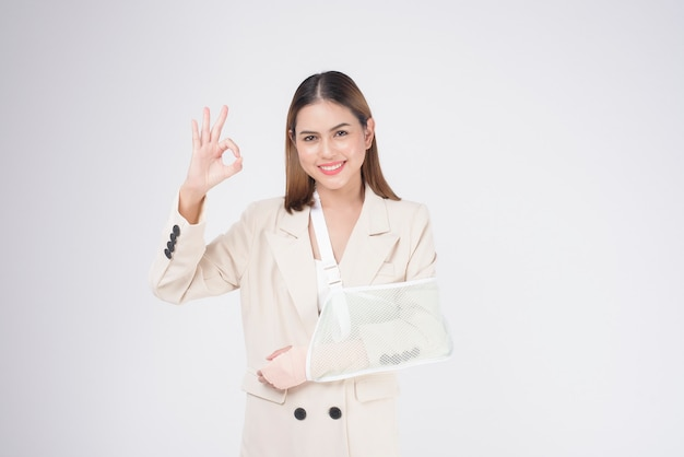 Portrait of young woman with an injured arm in a sling over white background in studio.