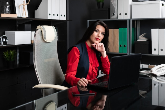 Portrait of young woman with laptop in office