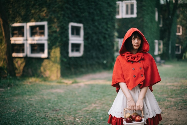 Portrait young woman with little red riding hood costume in green tree park