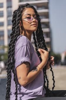 Ritratto di giovane donna con i capelli lunghi che indossa una camicia viola e occhiali da sole