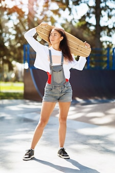 Portrait of young woman with a longboard in her hands in the park on a sunny summer morning