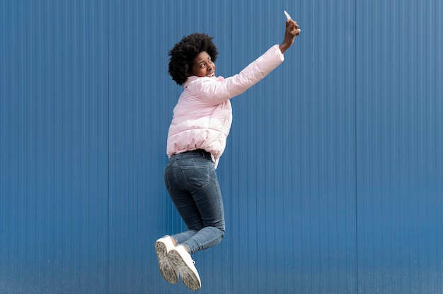 Portrait young woman with mobile jumping