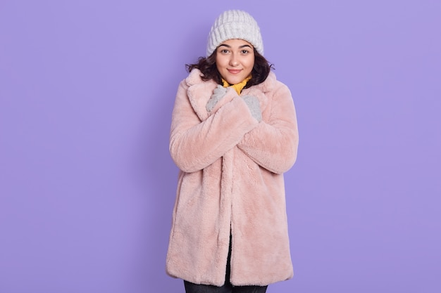 Portrait of young woman in with pale pink faux fur coat and cap, lady keeping hands on her collar and looking directly at camera, needs to warm, standing against lilac wall.