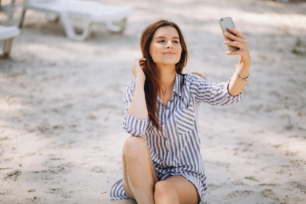 Portrait of a young woman with phone at the beach