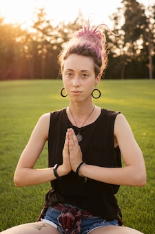 Portrait of young woman with pink dreadlocks doing yoga exercises outdoors and meditating in the park on sunset. lotus position