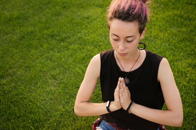 Portrait of young woman with pink dreadlocks doing yoga exercises outdoors and meditating in the park on sunset. top view. freedom and relaxation concept