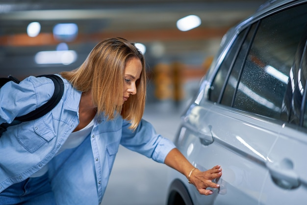 Portrait of young woman with scratched car at underground parking lot