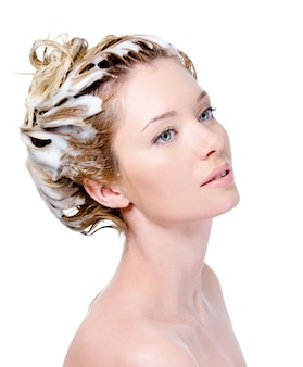 Portrait of young woman with soaping head with shampoo - white background