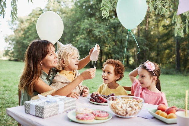 Portrait of young woman with son sitting at picnic table with group of kids during outdoor birthday ...