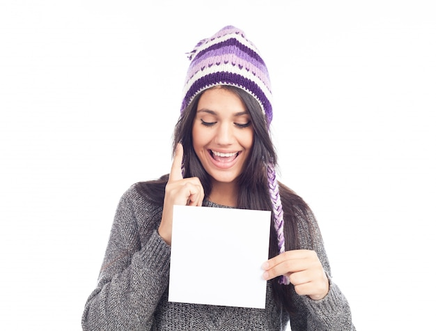 Portrait of young woman with a sweater and peruvian hat woolen holding sign card
