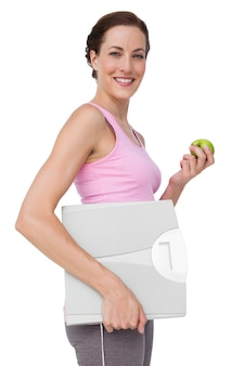 Portrait of a young woman with weight scale and apple