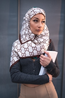 Portrait of an young woman with a white veil at the computer on the terrace of a coffee shop
