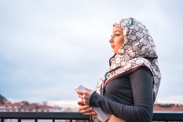 Portrait of an young woman with a white veil with a book on the terrace of a coffee shop, looking at the city from a balcony