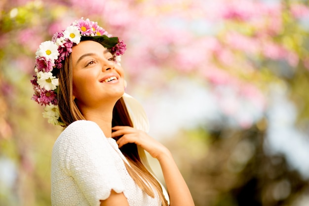 Portrait of young woman with wreath of fresh flowers on head in the park Premium Photo