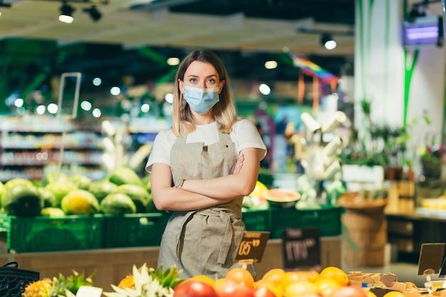 保護されたフェイスマスクの腕に立っている野菜セクションスーパーマーケットの肖像画の若い女性労働者の売り手が交差しました。果物屋の市場でカメラを見ている八百屋の女性仕事エプロンの従業員