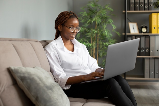 Portrait of young woman working on her laptop at a startup company