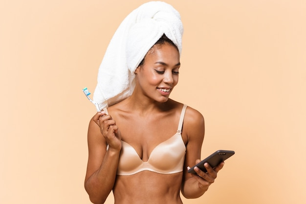Portrait of young woman wrapped in towel and wearing white lingerie brushing her teeth, while using smartphone isolated over beige wall