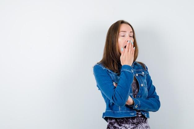 Ritratto di giovane donna che sbadiglia tenendo la mano sulla bocca in giacca di jeans, vestito e guardando assonnato vista frontale