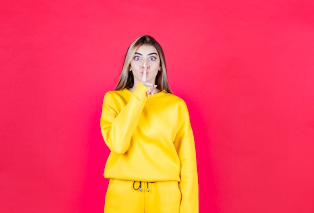 Ritratto di giovane donna in abito giallo che dà segno di silenzio