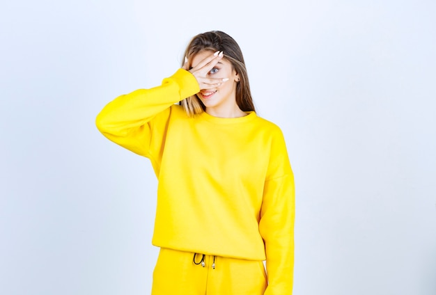 Portrait of young woman in yellow outfit standing and covering her eye
