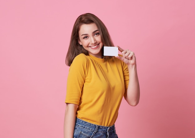 Portrait of a young woman in yellow shirt showing credit card and looking away at copy space isolated over pink .