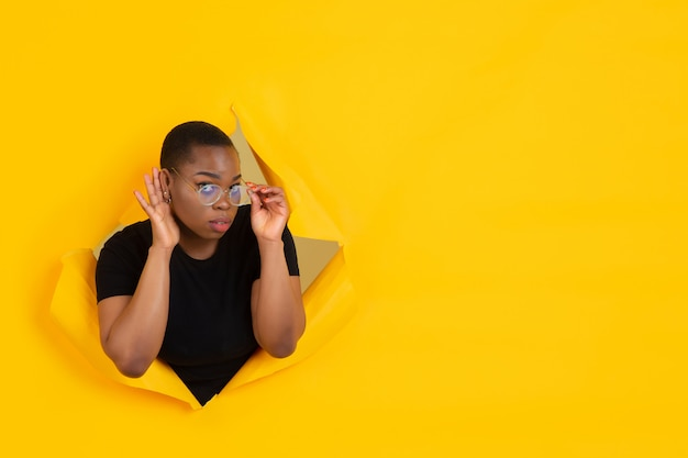 Portrait of young woman on yellow torn breakthrought background