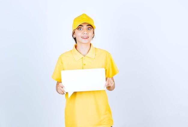 Ritratto di una giovane donna in uniforme gialla con un fumetto vuoto.