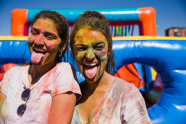 Portrait of a young women covered with holi face sticking out tongue looking at camera