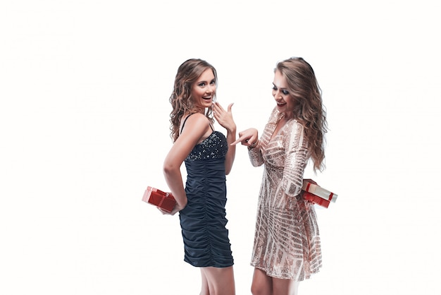 Portrait of young women friends holding gifts behind the back going to exchange them.
