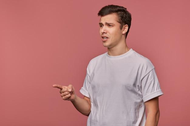 Ritratto di giovane ragazzo meravigliato indossa in maglietta vuota, mostra con il dito su qualcosa di incredibile, si leva in piedi sul rosa con spazio di copia, bocca spalancata in un'espressione scioccata.